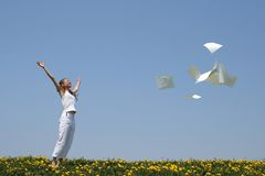 Free from paperwork. Laughing girl throws in air blank paper sheets (with copy space), freeing herself from paperwork Royalty Free Stock Photography