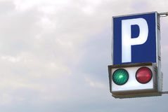Free parking. A traffic light for a parking against a stormy sky switched on the green light Stock Photos