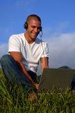 Free phone on computer. Young man working on computer (with phone) in grass land Royalty Free Stock Photo