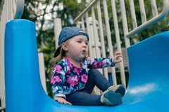 Caucasian cute girl play a slider in Playground in her schoolor kindergarten, kid and fun concept royalty free stock image