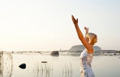 Free. Pretty blonde raising hands to the sun Stock Photography