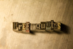 Free quotes - Metal letterpress lettering sign. Lead metal 'Free quotes' typography text on wooden background stock image