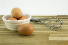 Free range eggs and whisk. Free range eggs in a white bowl and whisk on oak worktop Stock Images