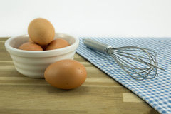 Free range eggs and whisk. Free range eggs in a white bowl and whisk on checked tablecloth Royalty Free Stock Photography