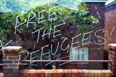 Free The Refugees, Graffiti on Glass Bus Shelter. Graffiti etched in a glass bus shelter wall; `FREE THE REFUGEES`, politically motivated vandalism Royalty Free Stock Photo
