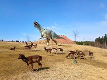 Free-roaming deer in dinosaur park with volcano royalty free stock image