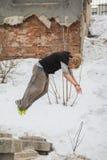 Free-run werk - het haarkerel van het tienerblonde de tik van de opleidings parkour sprong in het sneeuw behandelde park uit Royalty-vrije Stock Afbeelding