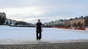 Free-running - blonde man tracer doing backflip in winter park, steadicam stock video