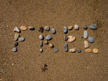 Free Sand. Free written with little rocks on the wet sand Royalty Free Stock Images