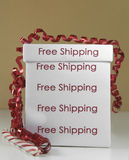 Free shipping box. Fancy free shipping box with a red curled ribbon and a candy cane stock image