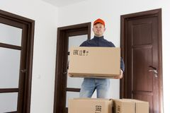 Free shipping concept. Courier delivery man with cardboard box in hands at apartment room of home. Royalty Free Stock Photo