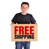 Free Shipping Man with Box on White. A man is holding a brown shipping box present that says Free Shipping. He is on a white background and looks happy Stock Photography