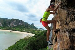 Free solo woman rock climber climbing. At seaside cliff stock photography