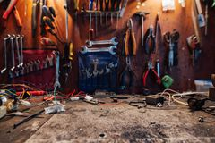 Free space on a dirty table in workshop, on the background of. Free space on a dirty table in the workshop, on the background of a hanging instrument stock images