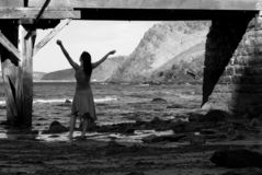 Free Spirit. A female expressing, with arms held high, barefoot in the shallows. Nice back drop Stock Photos