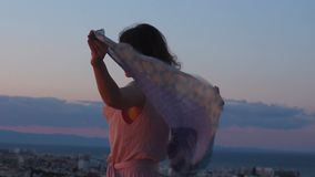 Free strong woman looking at cityscape at mountain bottom, wind playing her hair. Stock footage stock footage