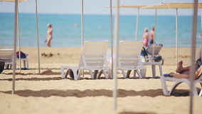 Free sunbeds on the beach near the sea.  stock footage