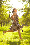Free time. Young beautiful woman jumping in a meadow Royalty Free Stock Photo