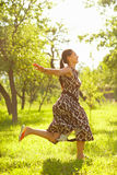Free time. Young beautiful woman jumping in a meadow Royalty Free Stock Photography