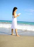 Free time. Walking alone on the beach while reading a bok and dreaming stock photo