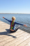Free time, enjoying the sun. Happiness of freedom, healthy lifestyle, leisure and relax near the water, suburban rest, the woman reaches for the sunlight and Royalty Free Stock Photo