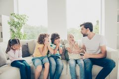 Free time preteen pre-teen concept. Babysitter tell scare story. Gesticulating hands and sit on couch in modern white light interior, children hold palms near stock photo