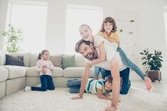 Free time, relax, rest concept. Little kids jump on daddy back f royalty free stock photos