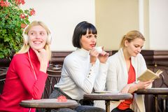 Free time spending. relax. business meeting. three girls do different things. different ways to relax. girls in cafe. Social diversity. listening music royalty free stock photos