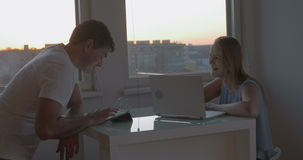 Free time with tablet PC and laptop. Young family couple having quiet evening at home. Woman and man talking while using pad and laptop stock video footage