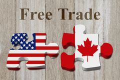 Free trade between USA and Canada. Two puzzle pieces with the flags of USA and Canada on weathered wood with text Free Trade stock photo