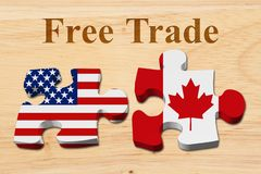 Free trade between USA and Canada. Two puzzle pieces with the flags of USA and Canada on wood with text Free Trade royalty free stock photography