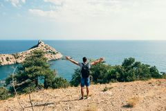Free traveler a man with a backpack stands. On the edge of the mountains to the sea, with their hands in nature Royalty Free Stock Images