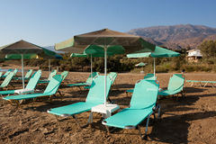 Free turquoise loungers under umbrellas Stock Image
