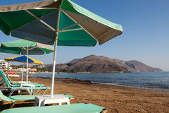 Free turquoise loungers under umbrellas on the sandy beach royalty free stock photos
