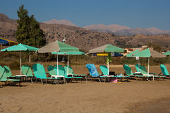 Free turquoise loungers under umbrellas Stock Images