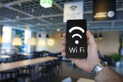 Free Wi-Fi. Modern smartphone in hand of man in cafe with free wifi. Man connecting smartphone to Wifi zone in cozy cafe. Badge and the inscription of wi fi in Stock Image