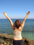 Free woman. A young woman at the coast feeling freedom. Backview Stock Image