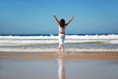 Free woman. Full body back view of a caucasian white woman in white dress raising up her arms and walking barefoot in the sea on a lonely tropical beach Royalty Free Stock Photo