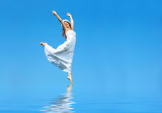 Free woman. Happy free young woman running across the water Royalty Free Stock Photography