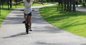 Free woman cycling at sunny morning park stock video