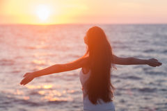 Free woman enjoying freedom feeling happy at beach at sunset. Beautiful serene relaxing woman in pure happiness and elated enjoyment with arms raised Royalty Free Stock Photos