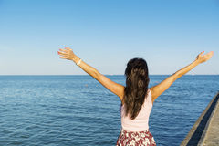 Free woman enjoying the summer with open arms on the beach Stock Photography
