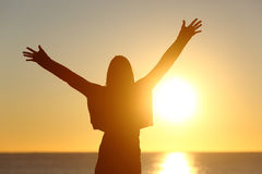 Free woman raising arms watching sun at sunrise royalty free stock photo
