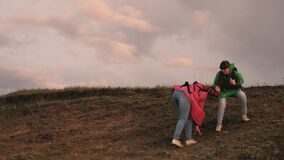 Free women travelers descend the top of the hill holding each other`s hands. teamwork travelers. The concept of