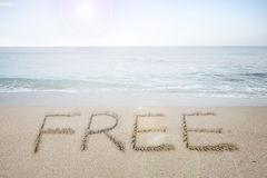 Free word handwritten in sand on sunny beach Royalty Free Stock Images