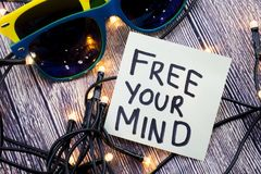 Free your Mind An encouragement concept on a note paper. Some lights are shown in discrete order. Two sunglasses of discrete color stock image