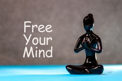 Free your mind - motivating text with white statuette of girl. Yoga and meditation concept.  royalty free stock photos