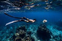 Freediver妇女滑动有飞翅和乌龟的水下的海洋 免版税库存照片