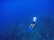 Freediver υποβρύχιο στη βαθιά μπλε θάλασσα Το άτομο κολύμβησης με αναπνευστήρα βουτά μέχρι την επιφάνεια νερού Στοκ Φωτογραφίες