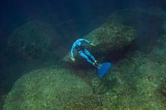 The freediver at the bottom of the sea. Near underwater rocks Royalty Free Stock Images